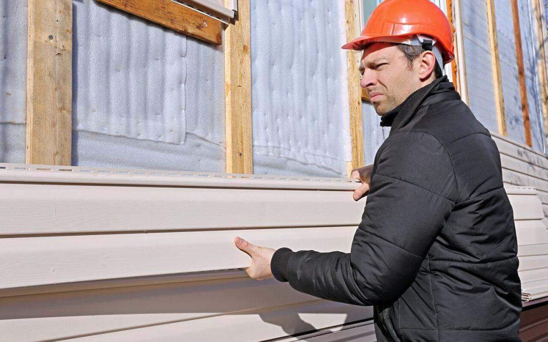A man installs home siding materials